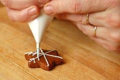 Mano de la mujer que adorna los dulces de la Navidad Imagen de archivo