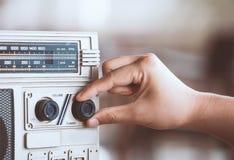 Mano de la mujer que ajusta el volumen de sonidos en el casete de radio retro foto de archivo