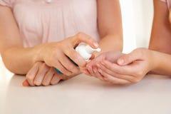 Mano de la mujer que aplica el desinfectante de la mano Imágenes de archivo libres de regalías