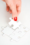 Mano de la mujer que cabe el pedazo correcto de rompecabezas que sugiere concepto del establecimiento de una red del negocio Foto de archivo