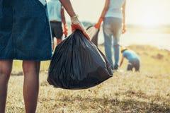 mano de la mujer que coge la basura y mano que celebra el bolso negro en el parque fotos de archivo libres de regalías