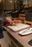 Mano de la mujer que corta el pan con un cuchillo imagen de archivo