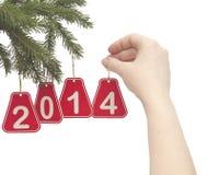 Mano de la mujer que cuelga un número 2014 en rama de árbol de abeto Imágenes de archivo libres de regalías