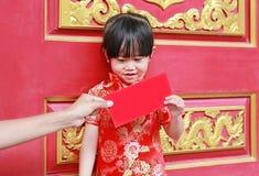 Mano de la mujer que da a paquete rojo el regalo monetario para la niña linda en el templo chino en Bangkok, Tailandia Concepto c foto de archivo libre de regalías
