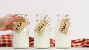 Mano de la mujer que elige el surtido del mercado de leche Foto de archivo