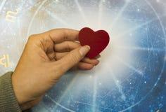 Mano de la mujer que guarda un corazón rojo sobre horóscopo azul como concepto de la astrología, del zodiaco y del amor fotos de archivo libres de regalías