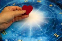 Mano de la mujer que guarda un corazón rojo sobre horóscopo azul como concepto de la astrología, del zodiaco y del amor imagen de archivo libre de regalías