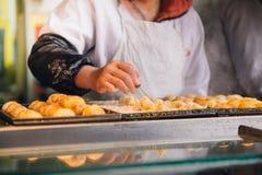 Mano de la mujer que hace takoyaki foto de archivo