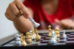 Mano de la mujer que juega el ajedrez para la táctica del negocio y la planificación hecha frente Imagen de archivo