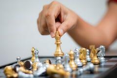 Mano de la mujer que juega el ajedrez para la táctica del negocio y la planificación hecha frente Fotografía de archivo