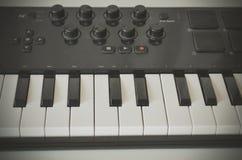 Mano de la mujer que juega el teclado de Midi del piano o del electone, la llave blanca y negra del sintetizador musical electrón Foto de archivo
