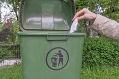 Mano de la mujer que lanza el papel arrugado en compartimiento imagen de archivo