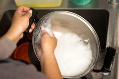 Mano de la mujer que lava el pote del acero inoxidable con el jabón que se lava del plato Fotografía de archivo