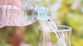 Mano de la mujer que lleva a cabo la botella de agua y la colada del agua potable clara en el vidrio en fondo verde borroso de la metrajes
