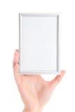 Mano de la mujer que lleva a cabo el marco de la foto aislado en blanco Imágenes de archivo libres de regalías