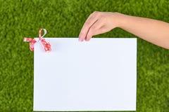 Mano de la mujer que lleva a cabo el papper blanco imagen de archivo libre de regalías