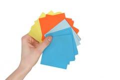 Mano de la mujer que lleva a cabo etiquetas engomadas de papel coloridas en el fondo blanco Imágenes de archivo libres de regalías