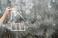 Mano de la mujer que lleva a cabo forma de la casa del dibujo de tiza en el muro de cemento Imagenes de archivo