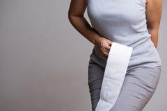 Mano de la mujer que lleva a cabo su parte inferior y tejido o rollo del papel higiénico Desorden, diarrea, estreñimiento Concept fotografía de archivo