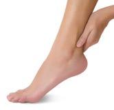 Mano de la mujer que lleva a cabo su pie sano hermoso y que da masajes al tobillo en área del dolor Foto de archivo libre de regalías