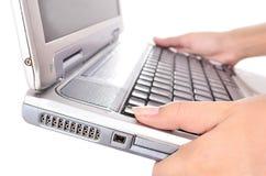 Mano de la mujer que lleva un ordenador portátil, aislado en blanco Imagen de archivo