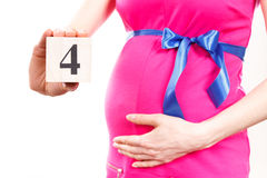 Mano de la mujer que muestra número de cuarto mes del embarazo, esperando para el concepto recién nacido Imagen de archivo
