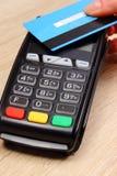 Mano de la mujer que paga con la tarjeta de crédito sin contacto con la tecnología de NFC, concepto de las finanzas fotos de archivo libres de regalías