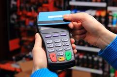 Mano de la mujer que paga con la tarjeta de crédito sin contacto, tecnología de NFC imagen de archivo libre de regalías