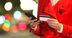 Mano de la mujer que paga en línea en una noche del invierno