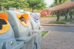 Mano de la mujer que pone la botella plástica usada en papeleras de reciclaje públicas o cubos de la basura segregados en parque  imagen de archivo libre de regalías