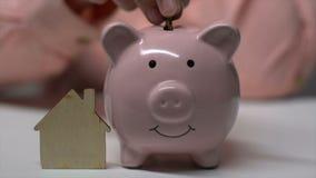Mano de la mujer que pone la moneda en el piggybank cerca de poca casa de madera, donaci?n de la caridad almacen de metraje de vídeo