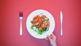 Mano de la mujer que pone la placa con la ensalada vegetal en la tabla, aperitivo vitaminado almacen de video