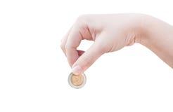 Mano de la mujer que pone una moneda aislada en el fondo blanco fotografía de archivo libre de regalías