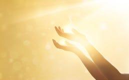 Mano de la mujer que ruega para bendecir de dios en puesta del sol foto de archivo