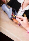 Mano de la mujer que se considera de la tarjeta de crédito en terminal del pago fotos de archivo