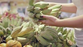 Mano de la mujer que selecciona plátanos verdes en el supermercado Mujer que toma un manojo de plátanos adentro de un colmado Chi almacen de video