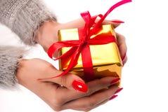 Mano de la mujer que sostiene la caja de oro presente con el arco rojo Imagen de archivo libre de regalías