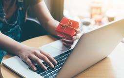Mano de la mujer que sostiene la caja de regalo roja sobre concepto en línea que hace compras Fotos de archivo