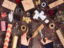 Mano de la mujer que sostiene la cinta de la arpillera con las tijeras para la caja de regalo de la Navidad que corta y de empaqu Imagen de archivo libre de regalías