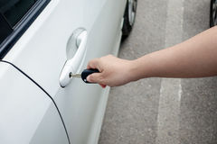 Mano de la mujer que sostiene el coche de la puerta para desbloquear o para cerrarse Imágenes de archivo libres de regalías