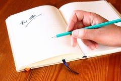Mano de la mujer que sostiene el lápiz y el cuaderno abierto con a para hacer la lista. Fotos de archivo libres de regalías