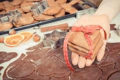 Mano de la mujer que sostiene el pan de jengibre o las galletas por tiempo de la Navidad y los accesorios frescos para cocer Fotografía de archivo