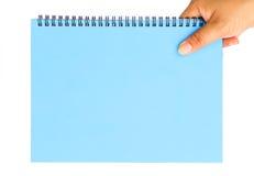 Mano de la mujer que sostiene el papel en blanco azul Imagen de archivo
