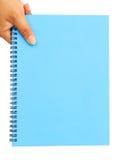 Mano de la mujer que sostiene el papel en blanco azul Fotos de archivo
