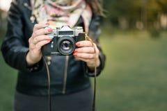 Mano de la mujer que sostiene el primer retro de la cámara en el fondo del otoño Imagen de archivo
