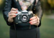 Mano de la mujer que sostiene el primer retro de la cámara en el fondo del otoño Fotografía de archivo
