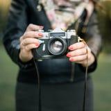 Mano de la mujer que sostiene el primer retro de la cámara en el fondo del otoño Fotos de archivo libres de regalías