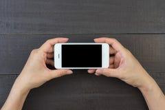 Mano de la mujer que sostiene el teléfono elegante Fotografía de archivo libre de regalías
