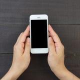 Mano de la mujer que sostiene el teléfono elegante Foto de archivo libre de regalías