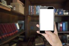 Mano de la mujer que sostiene el teléfono elegante con el pulgar que empuja el botón Fotos de archivo libres de regalías